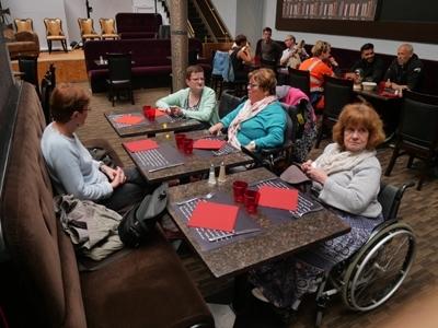 Photo montrant des personnes en situation de handicap attablées dans la salle de restaurant